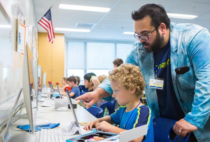 Teacher helping student work on tablet